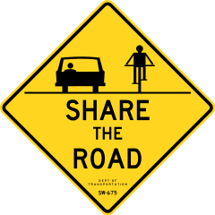 car and bike next to each other on sign saying share the road